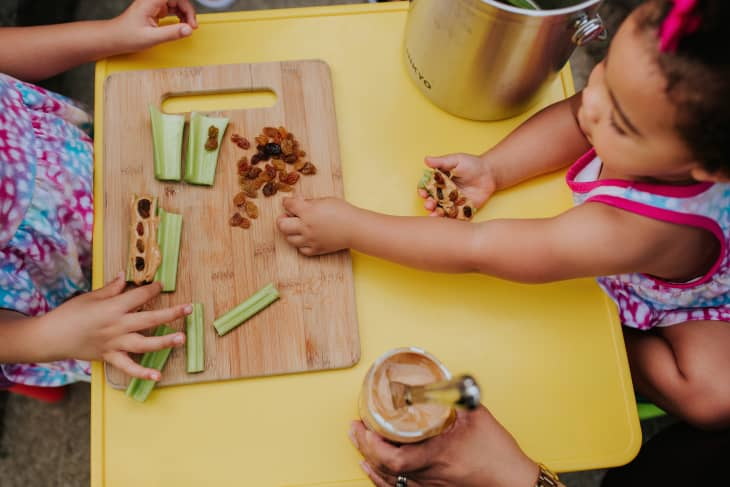 Yolanda's daughters making the snack ants on a log