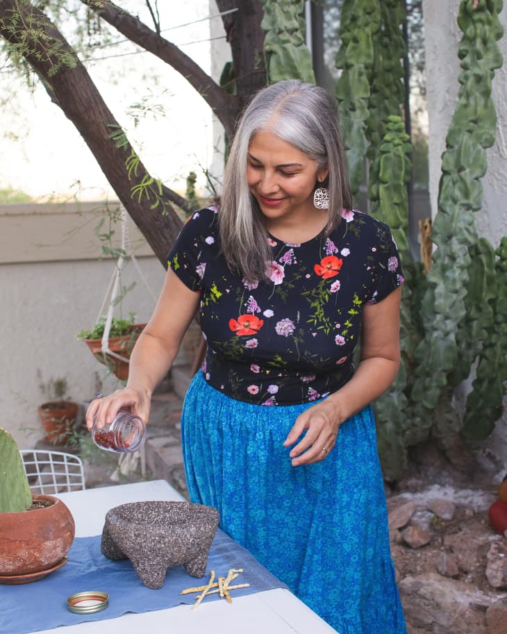 Felicia adding some seeds to her molcajete