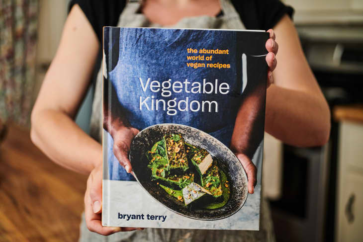 Someone holding up front cover of Bryant Terry's Vegetable Kingdom cookbook