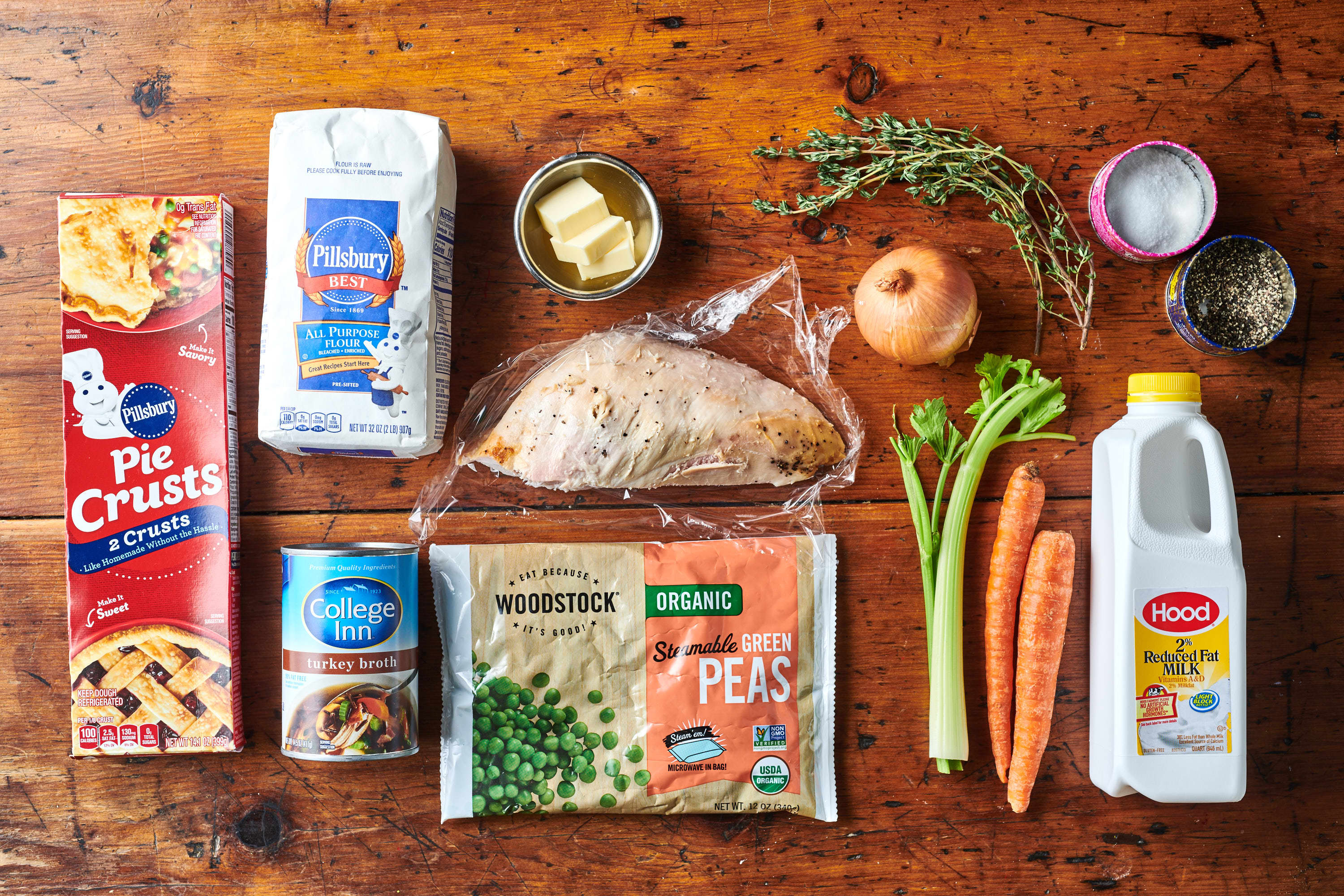 Ingredients for Leftover Turkey Potpie laid out; clockwise; salt and pepper, buttermilk, carrots, celery, peas, turkey stock, pie crust, flour, butter, onion, thyme.  Turkey breast in center.