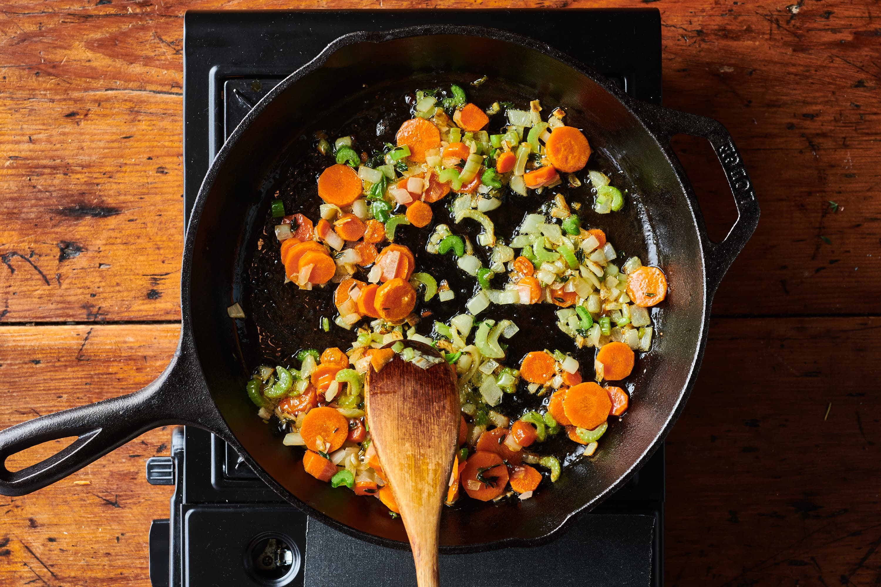 Carrots, celery and onion cooking in skillet.