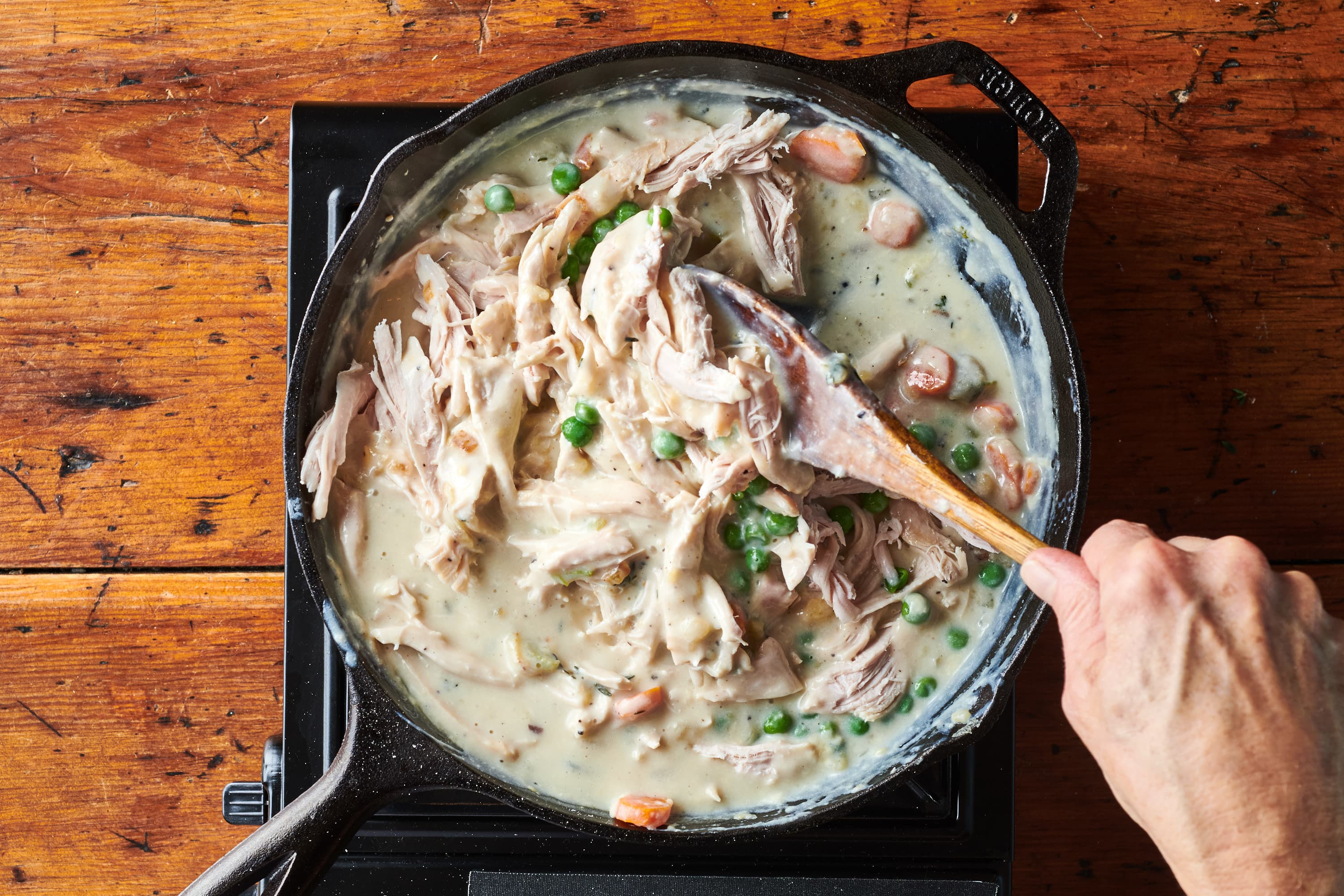 Turkey stirred into pot pie filling cooking in skillet.