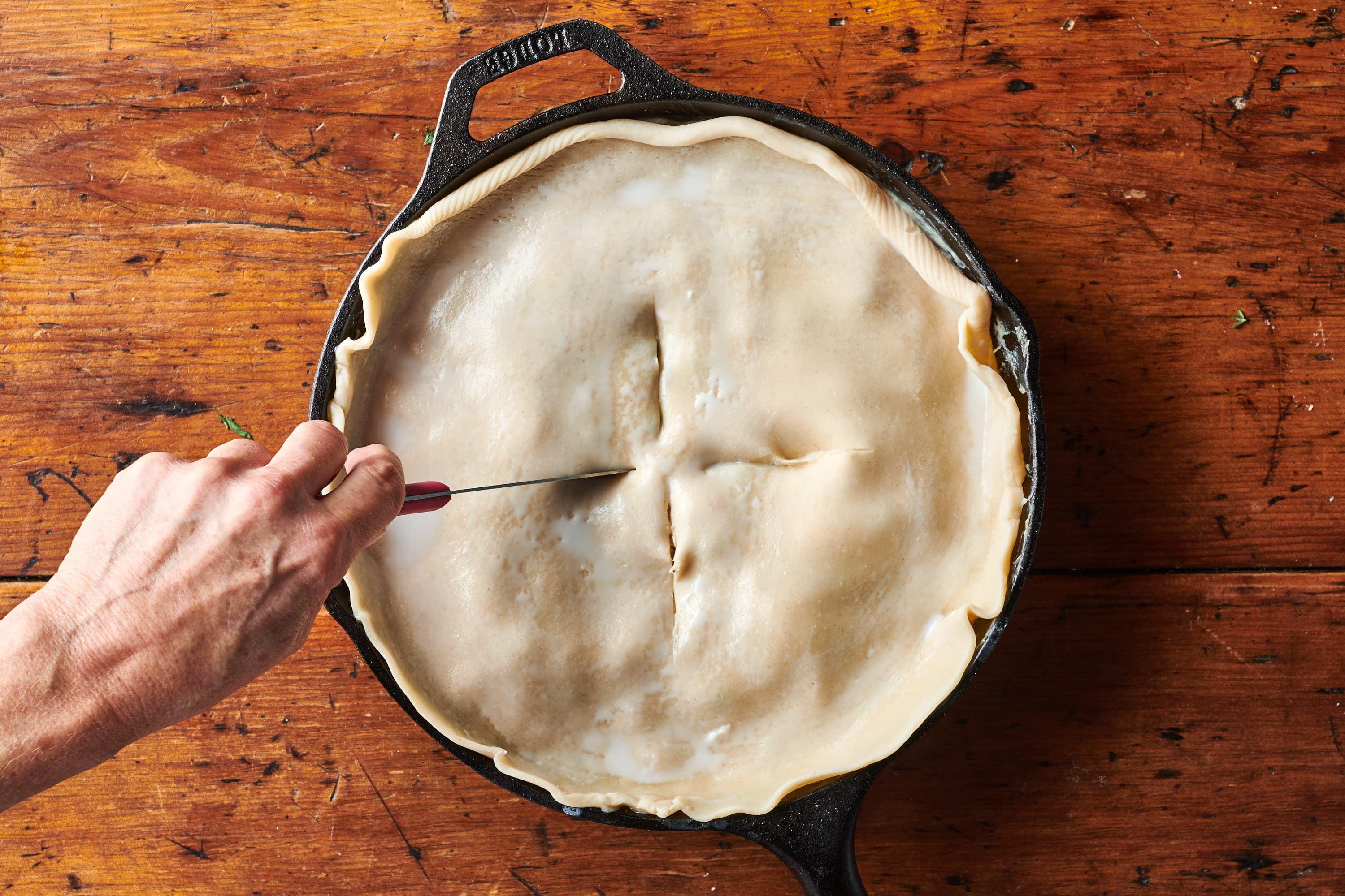 Someone slices steam holes into top of pie crust for turkey pot pie.