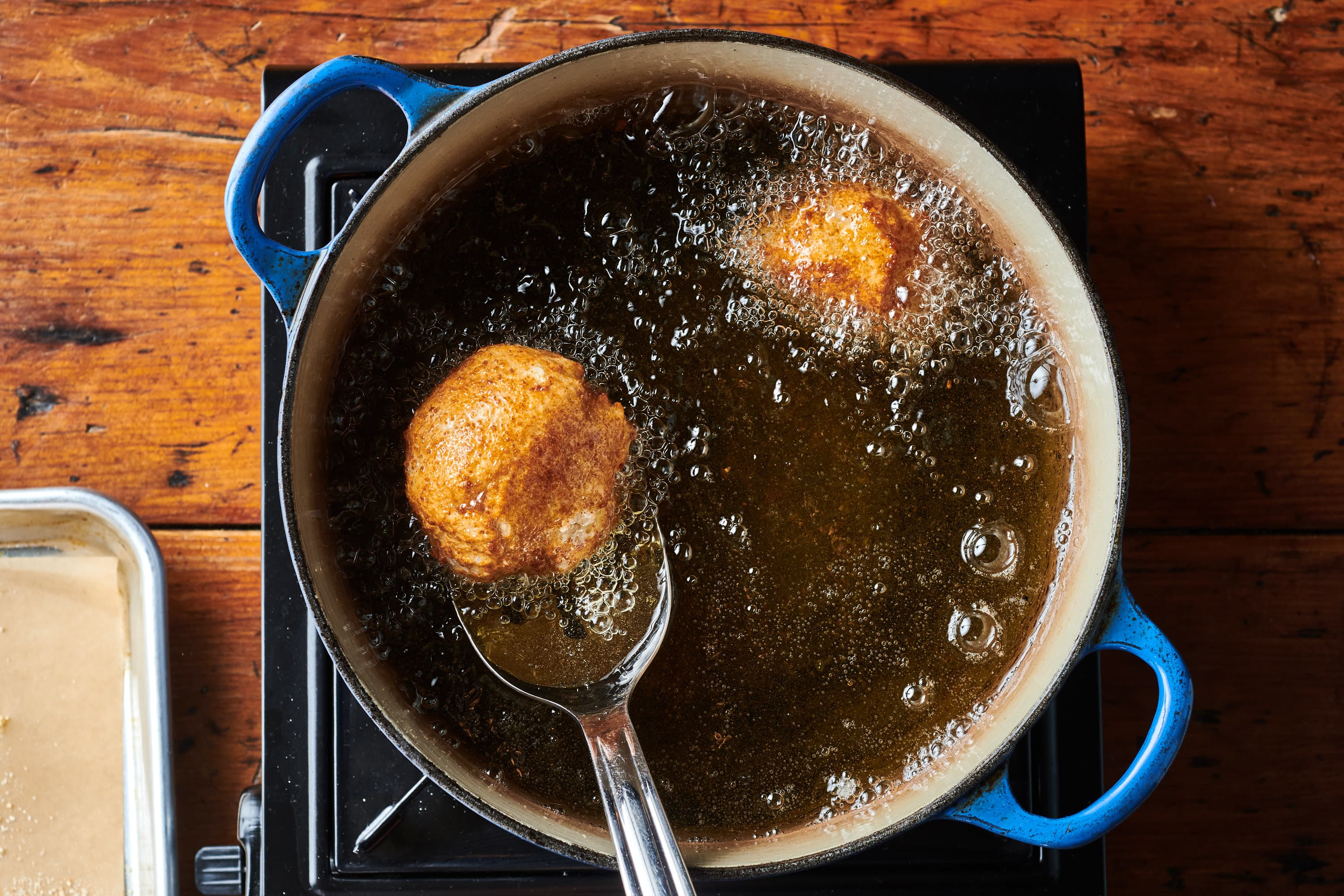 Mashed potato croquettes frying in oil.