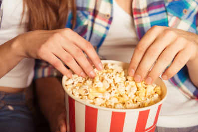 Two hands reaching for popcorn