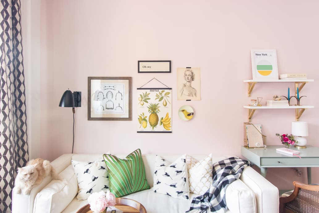 pink room with sofa, pillows, and art