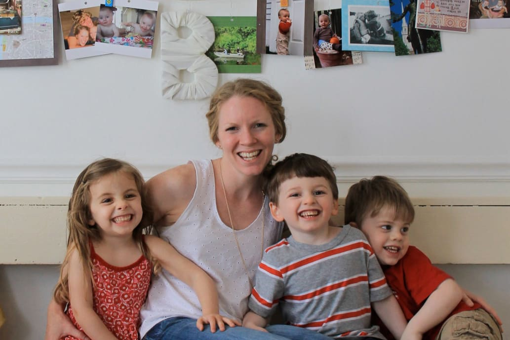 Mother and three kids seated in front of artwork clipped to a wire hanging on the wall