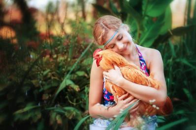 Girl Cuddling a Chicken