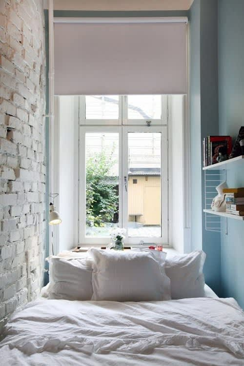 Small Blue Bedroom with White Exposed Brick and Window