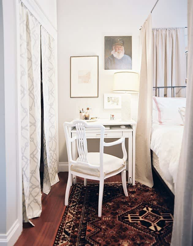 White Bedroom with Persian Rug and White Desk Next to Canopy Bed