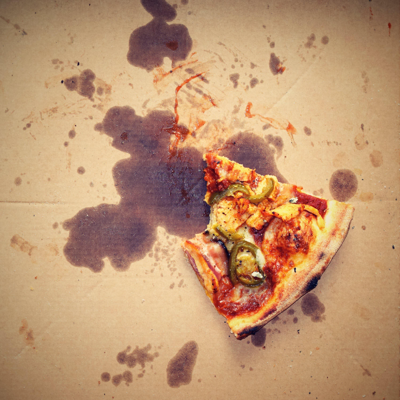 Half of a greasy pizza slice in a box