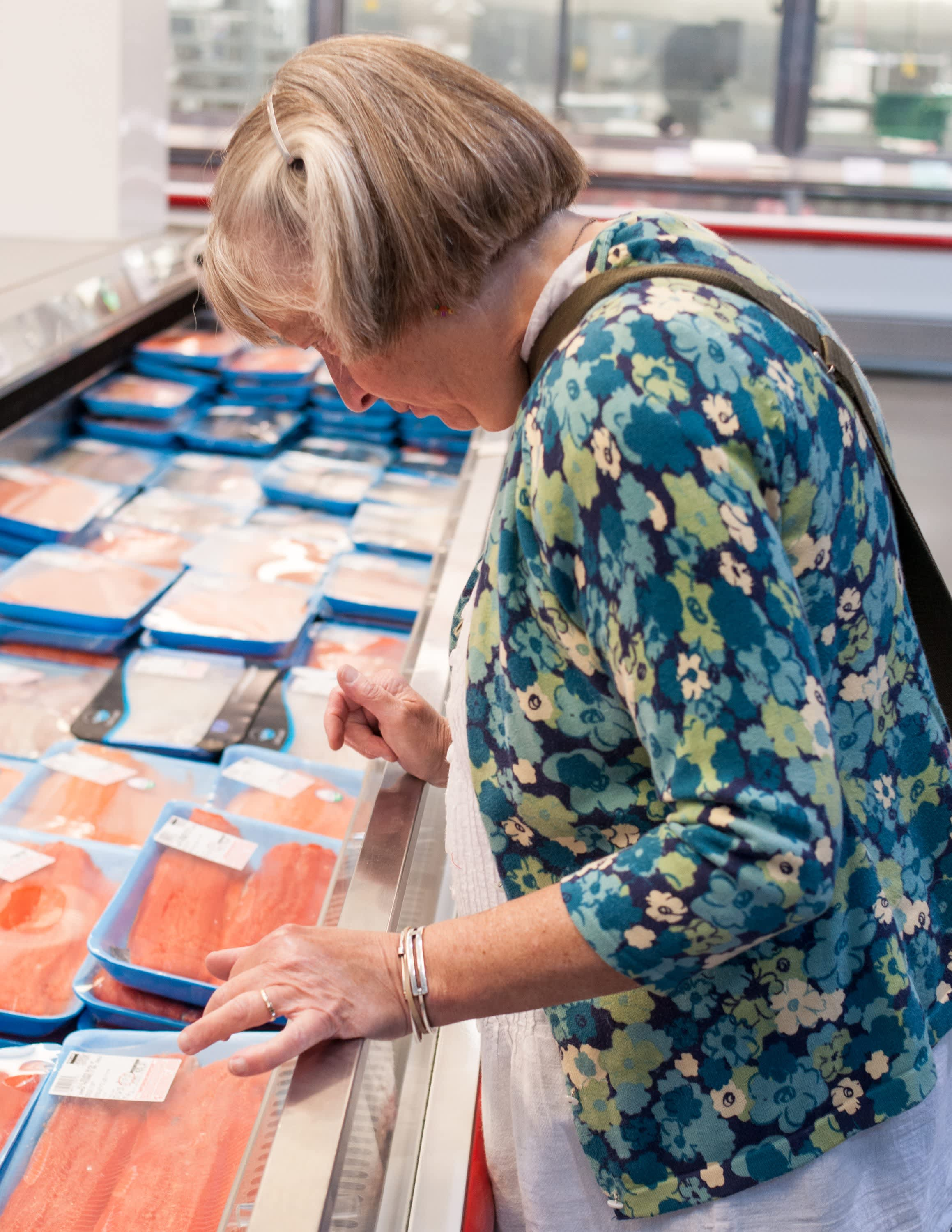 Woman choosing salmon from a refrigerator case