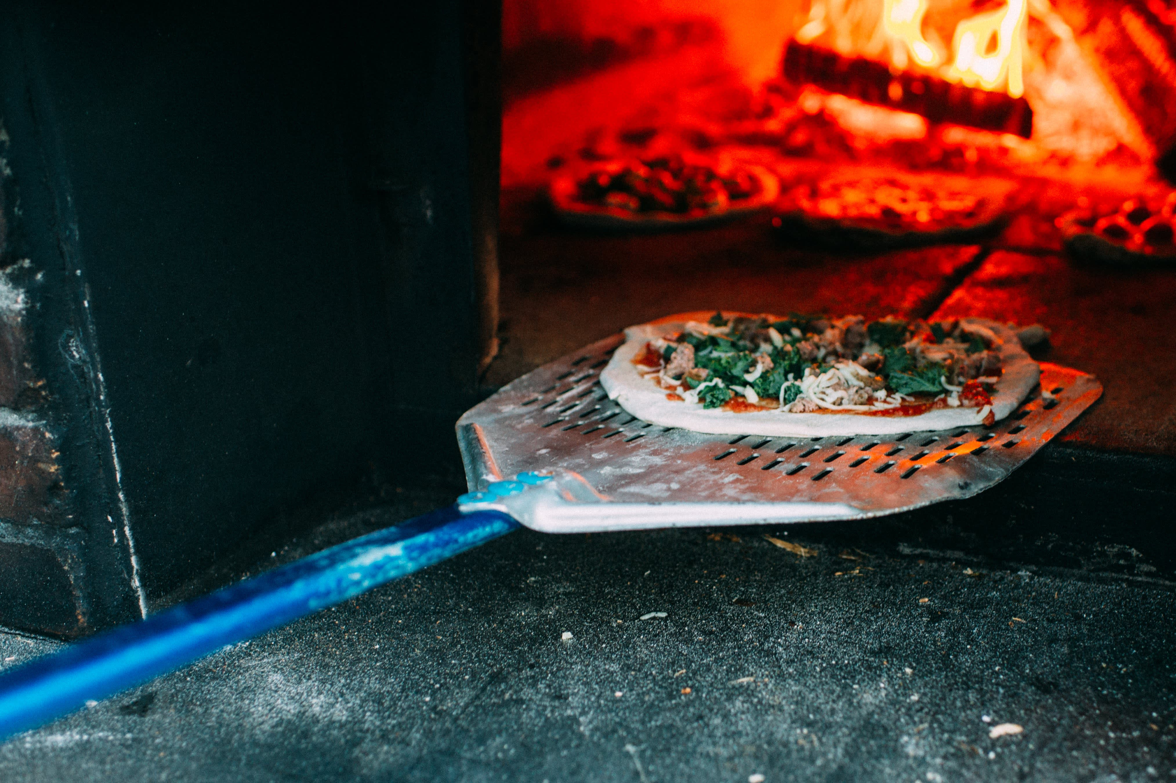 Pizza Going into the Wood-Fired Oven