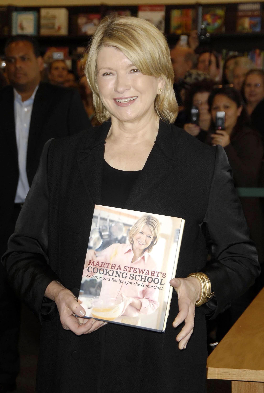 Martha Stewart holding her book