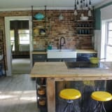 Kitchen after remodel with exposed brick and farmhouse sink