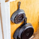 Cast iron pans hanging on a cabinet