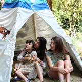 A mother and two daughters sit in a teepee under a tree.