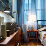 a moody corner of a vintage-filled bedroom