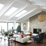 A bright, modern living room with sofa, fireplace and pendant light.