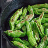 Half-cooked blistered peppers in a skillet