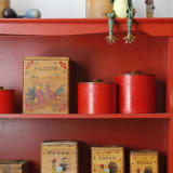 a crimson red cabinet in a kitchen with vintage knick-knacks and collectibles on it.