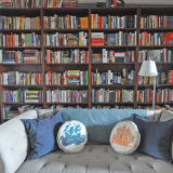 a wall shelves lined with books and a cozy tufted gray sofa perfect for reading