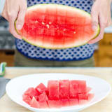 Removing cubed watermelon from the rind