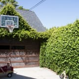 Concrete driveway with basketball hoop and two small children in a wagon