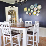 dining room with white dining set and a collection of brightly colored plates displayed on a dark navy walls