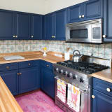 Blue kitchen cabinets and tile backsplash