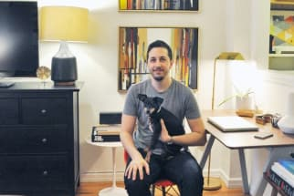 man and his small dog sitting in a stylish studio apartment with vintage artwork and hardwood floors