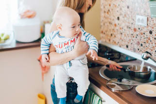 Woman in kitchen holding baby
