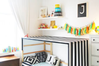 An IKEA Kura bed hack in a child's room featuring a black and white striped fabric canopy.