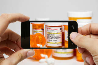 someone taking a photo of medicine bottles with an iphone
