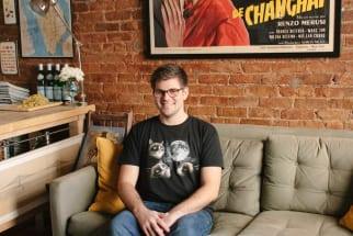 man in grumpy cat shirt sitting on sofa in front of an exposed brick wall with a framed vintage french movie poster