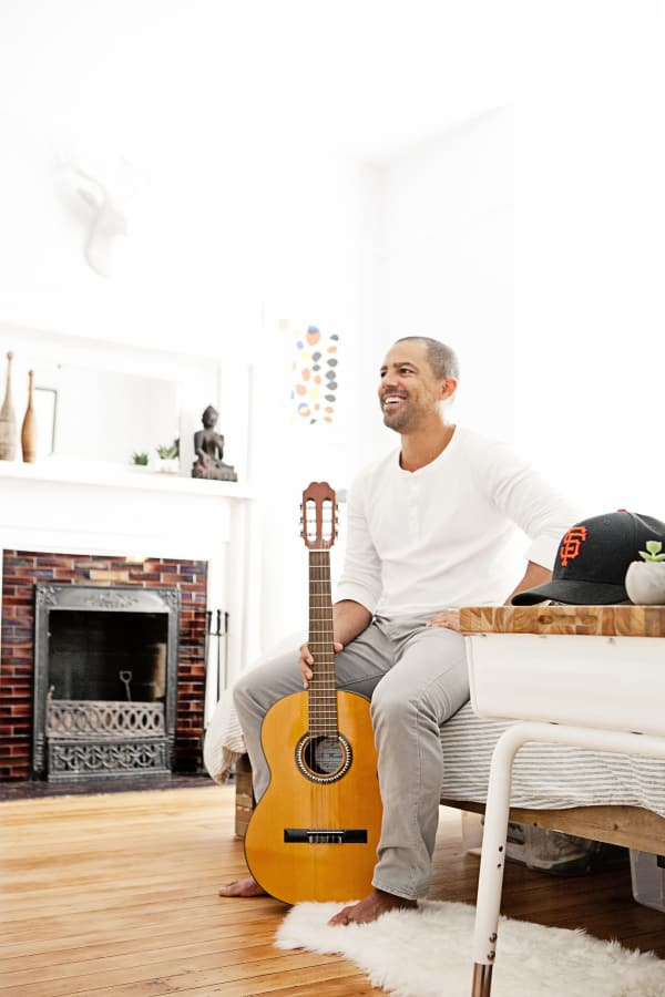 man with guitar sitting in all white room with fireplace, hardwood floors and a flokati rug