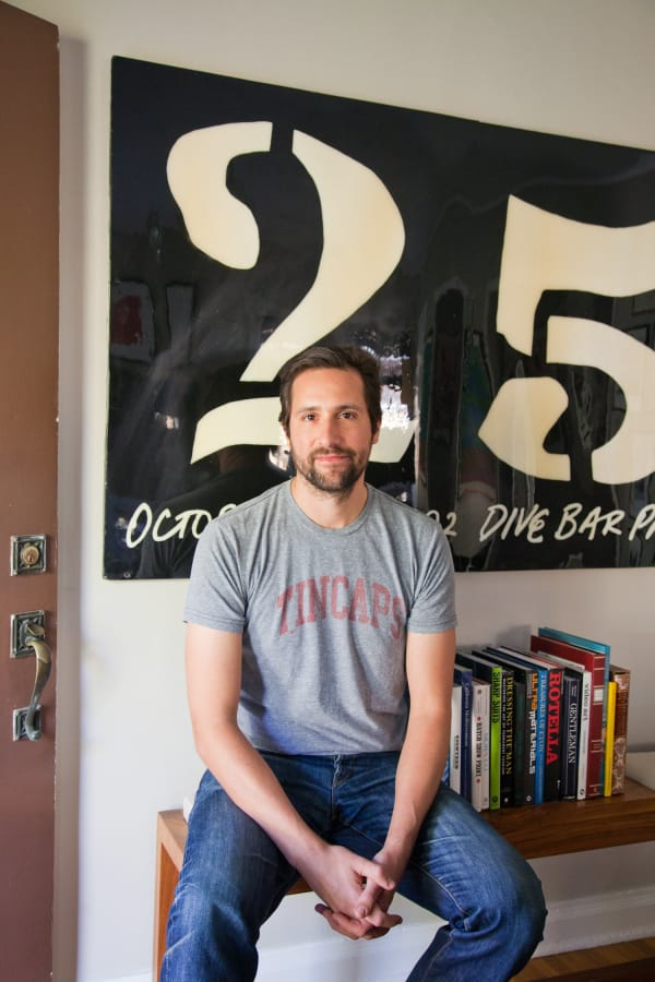 man sitting on an entryway bench in front of bold black and white artwork featuring the number 25