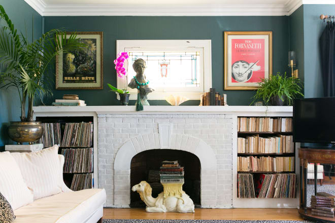 The fireplace with shelves, typical of Logan Square apartments is filled with their collection of records and books. The original stained glass windows flanked with prints by two favorite artists, Jean Cocteau & Piero Fornasetti purchased at Jean Cocteaus home at Milly-la-Foret and the Fornasetti exhibit in Paris.