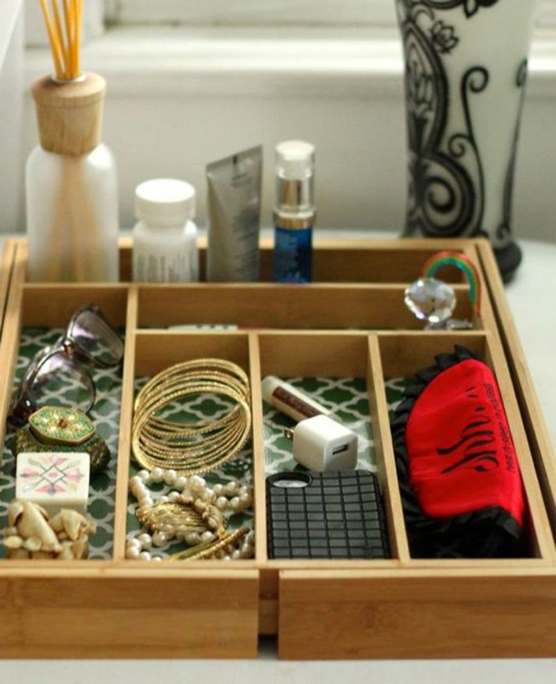 Wooden drawer organizer being used as a bedside valet for women's accessories.