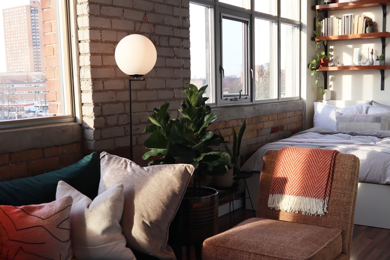 A 450-Square-Foot Studio Apartment Has Gorgeous Brick Walls & Coziest Bed Nook