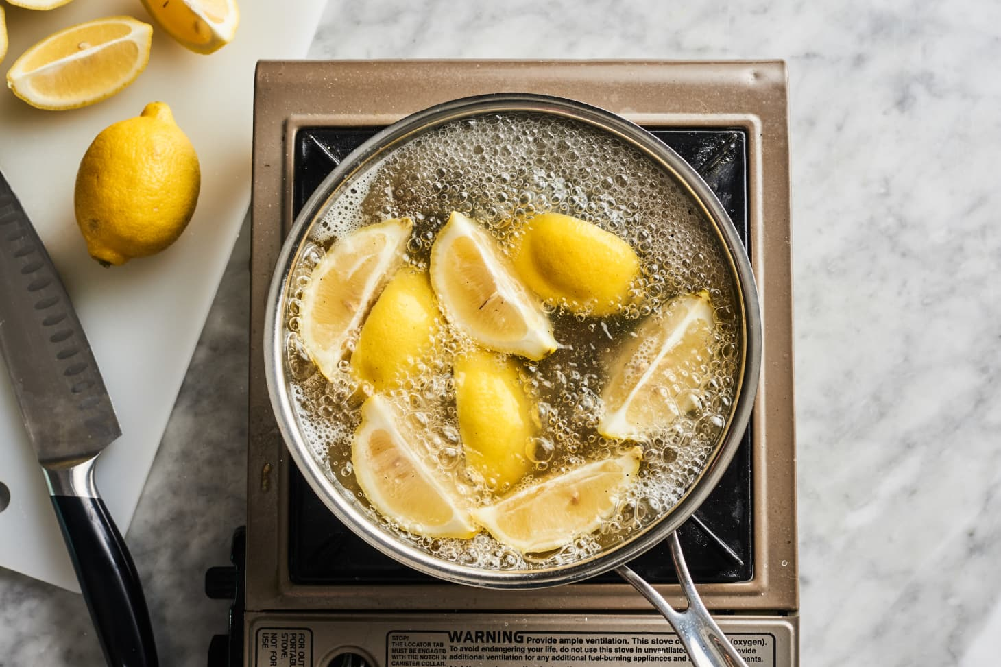 Boiling mixture of lemons and water to clean burnt pot
