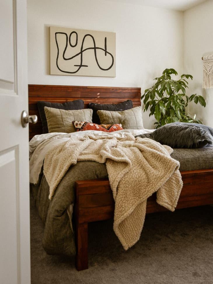 Bed with grey-green comforter and plush tan throw. Abstract artwork above headboard.