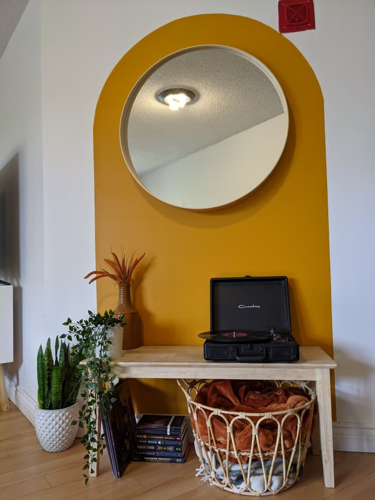 Circular mirror centered in gold painted arch shape in hallway