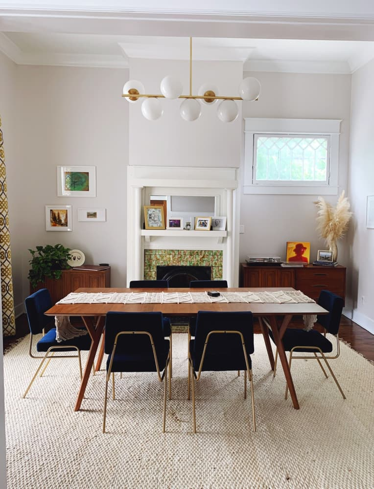 Eclectic dining room with West Elm globe chandelier, velvet blue upholstered dining chairs, and mid-century modern inspired wood furniture