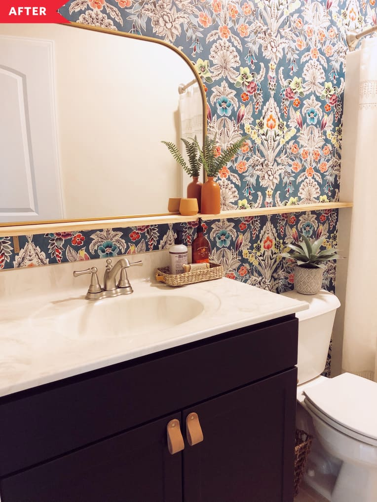 After: bathroom with black vanity, colorful patterned wallpaper, and a shelf for the mirror
