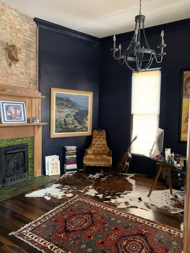 Dark blue walls and eclectic furniture with a brick fireplace in a living room