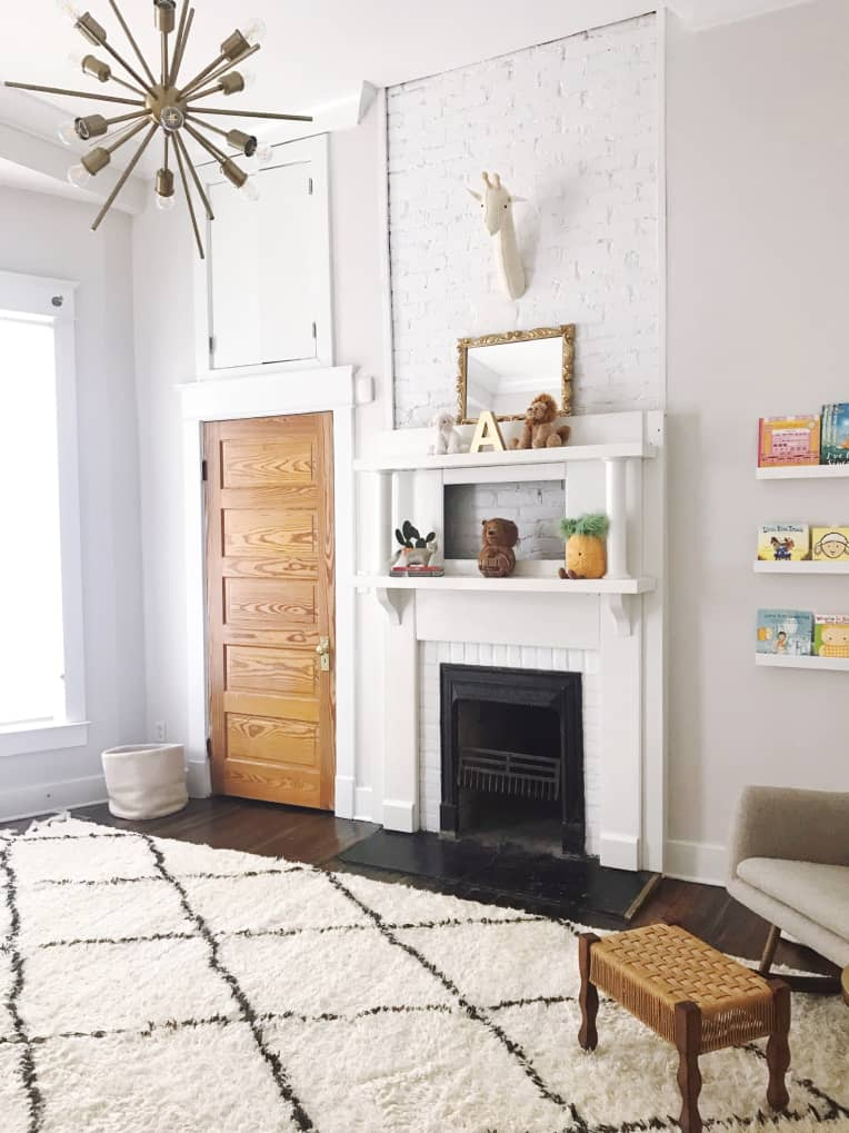 All white nursery with sputnik chandelier, beni ourain rug, fireplace, and eclectic furniture