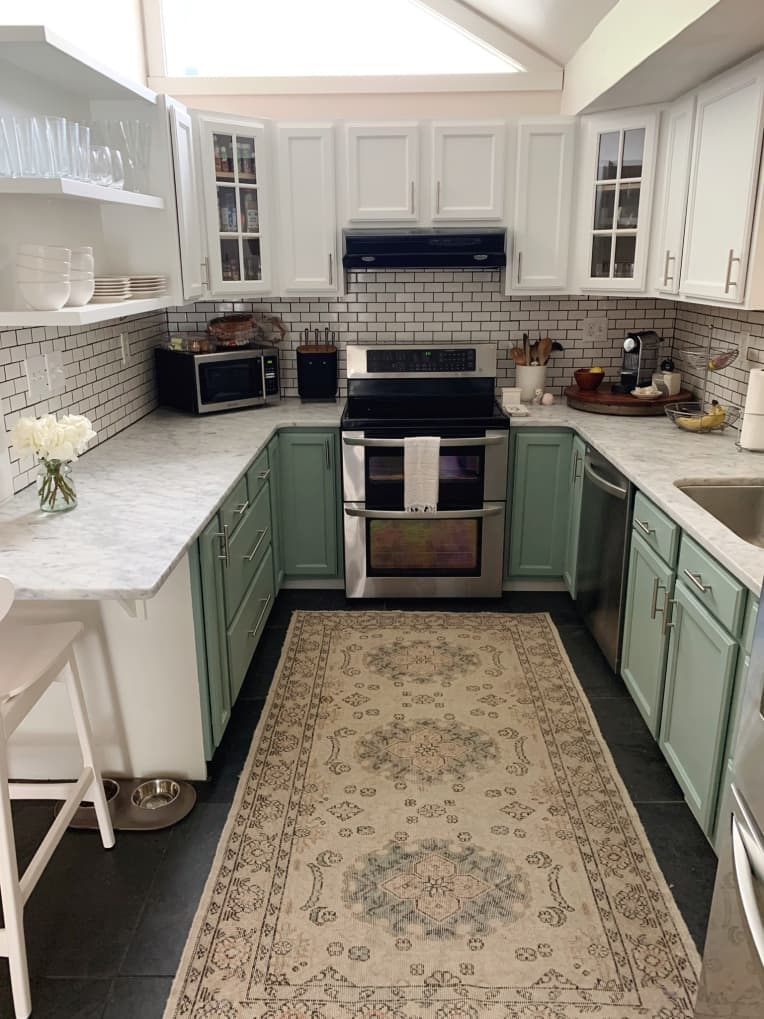 Traditional farmhouse style kitchen with mint green bottom cabinets and white upper cabinets and white subway tile