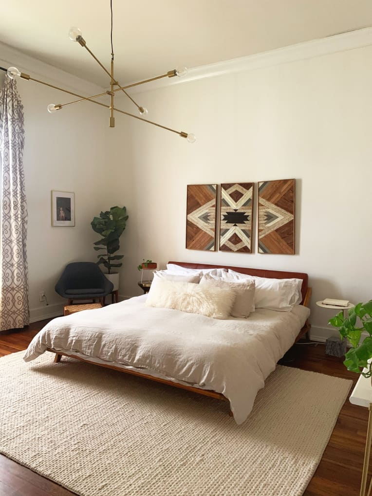 Neutral bohemian bedroom with modern brass chandelier and wood art piece above bed