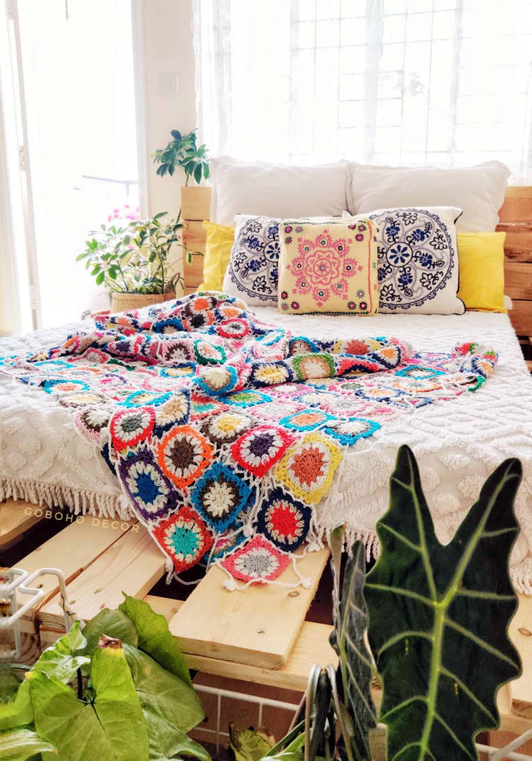 Pallet bed wtih colorful throw and patterned pillows